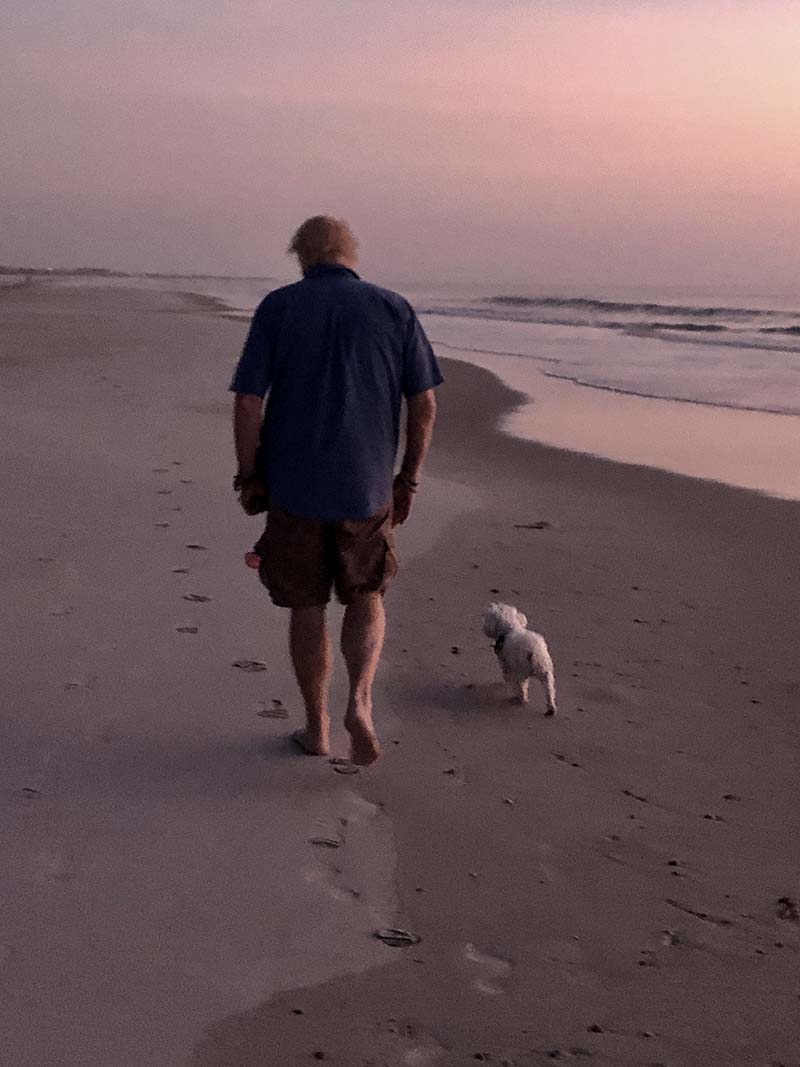 Chuck Strozier on the beach walking his dog